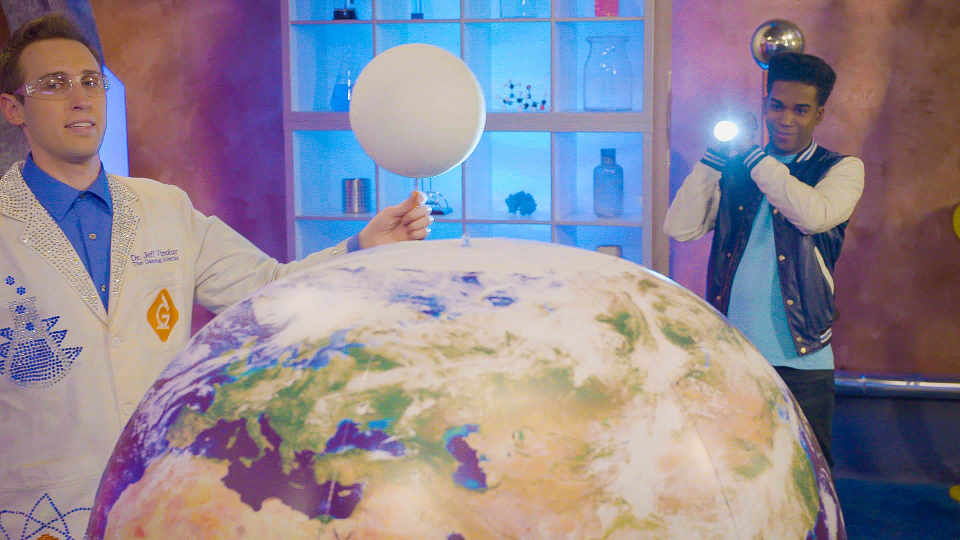 scientist and kids demonstrate how the phases of the moon are seen