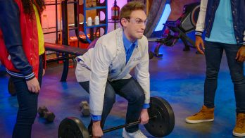 scientist lifts a weight to demonstrate use of muscles