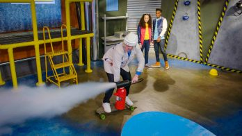 scientist demonstrates unbalanced forces using a fire extinguisher