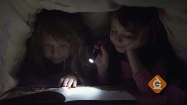 kids read books with flashlight under covers