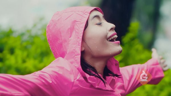 woman shows that a raincoat is made of material that does not get wet