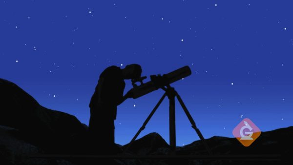 man looks at the night sky through a telescope