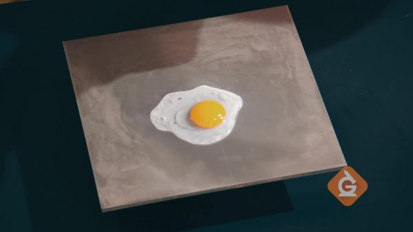 egg is cooked on a piece of metal
