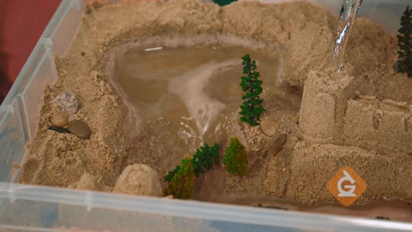 scientific demonstration of water erosion washing away trees
