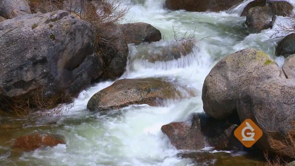 water flowing over rocks and making them smooth through erosion