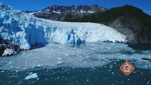aerial view of a glacier moving into the water