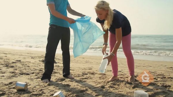 people picking up garbage on the beach