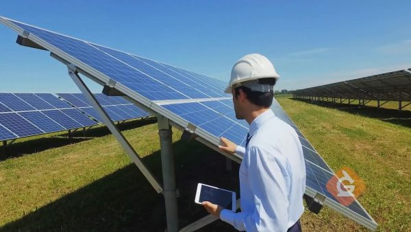 man inspects solar cells which generate electricity from the sun